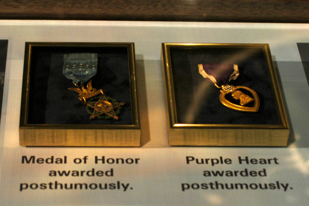 A Medal of Honor and a Purple Heart medal are in separate cases, side-by-side in a display.