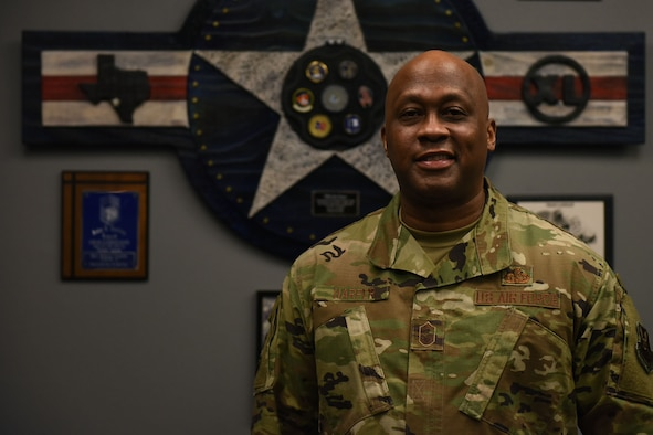 Chief Master Sgt. Ronald Harper poses for a portrait photo inside of his office, looks directly at the camera and smiles.