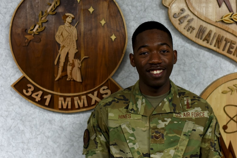 Staff Sgt. Khalif Hines stands in front of a maintenance squadron emblem and looks directly at the camera as he smiles for the photo.
