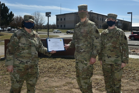 U.S. Air Force Col. Angelina Maguinness, 17th Training Group commander, presents Airman Aidan Pilkington, 312th Training Squadron student, the 17th TRG Student of the Month award outside of Brandenburg Hall on Goodfellow Air Force Base, Texas, Feb. 26, 2021. Pilkington worked hard for his award and has shown dedication to his squadron and the training he received at Goodfellow. (U.S. Air Force photo by Senior Airman Ashley Thrash)