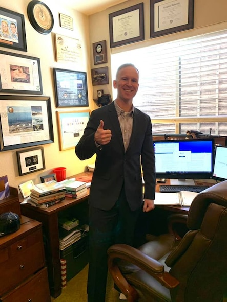 Man gives the camera a thumbs up following his successful dissertation defense.