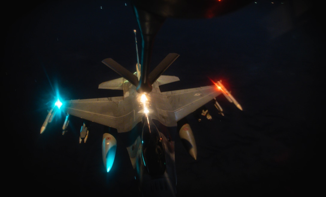 An airborne aircraft with red and blue lights receives fuel at night.