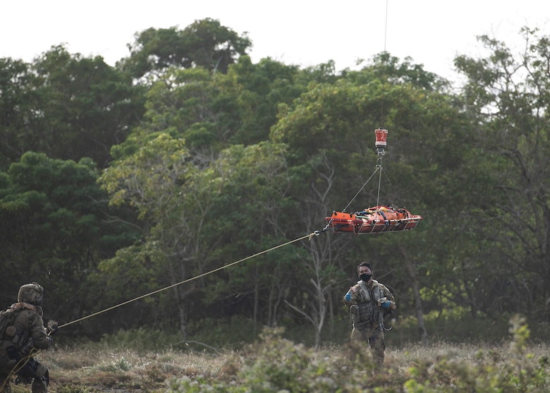 A U.S. Airmen of the 644th Combat Communications Squadron runs the trail line of the stretcher as it's hoisted in to the Guam Army National Guard helicopter during Exercise Dragon Shield at Northwest Field, Guam, January 13, 2021.