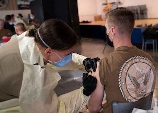 U.S. Army Staff. Sgt. Kristin Zimmerman, a civil affairs team medic with Civil Affairs East Africa, administers the COVID-19 vaccine at Camp Lemonnier, Djibouti.