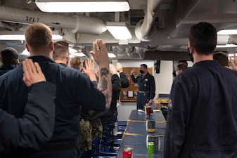 Command Master Chief Logan Johnson, command master chief aboard the Arleigh Burke-class guided-missile destroyer USS Mitscher (DDG 57), leads Sailors in reaffirming the oath of enlistment during a stand-down for countering extremism in the ranks.
