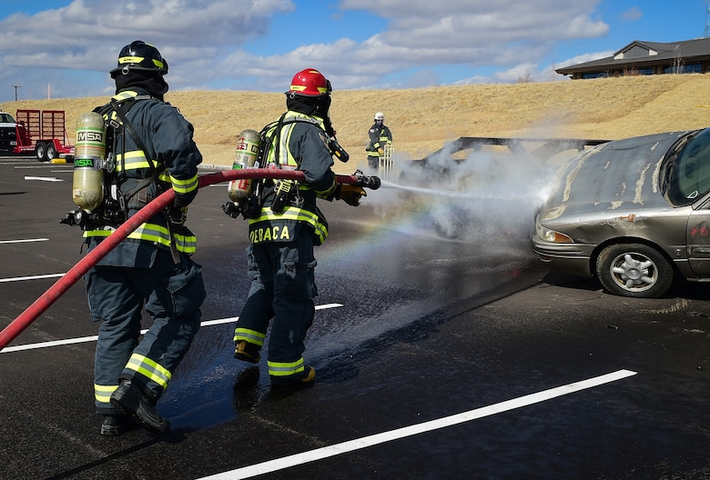 Fire Lt. Christopher Debaca and Dusty Smock, both firefighters from the 460th Civil Engineer Squadron, hose down a burning vehicle during an auto extraction exercise on Buckley Air Force Base, Colo., Feb. 24, 2021.