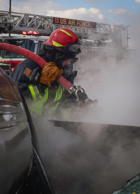 Fire Lt. Christopher Debaca, a firefighter with the 460th Civil Engineer Squadron, hoses down a burning vehicle during an auto extraction exercise on Buckley Air Force Base, Colo., Feb. 24, 2021.
