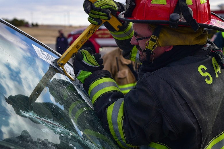Fire Lt. Chris Gay, the training cordinator for the Sable Altura Fire Rescue, saws into the windshield of a car during an auto extraction exercise on Buckley Air Force Base, Colo., Feb. 24, 2021.