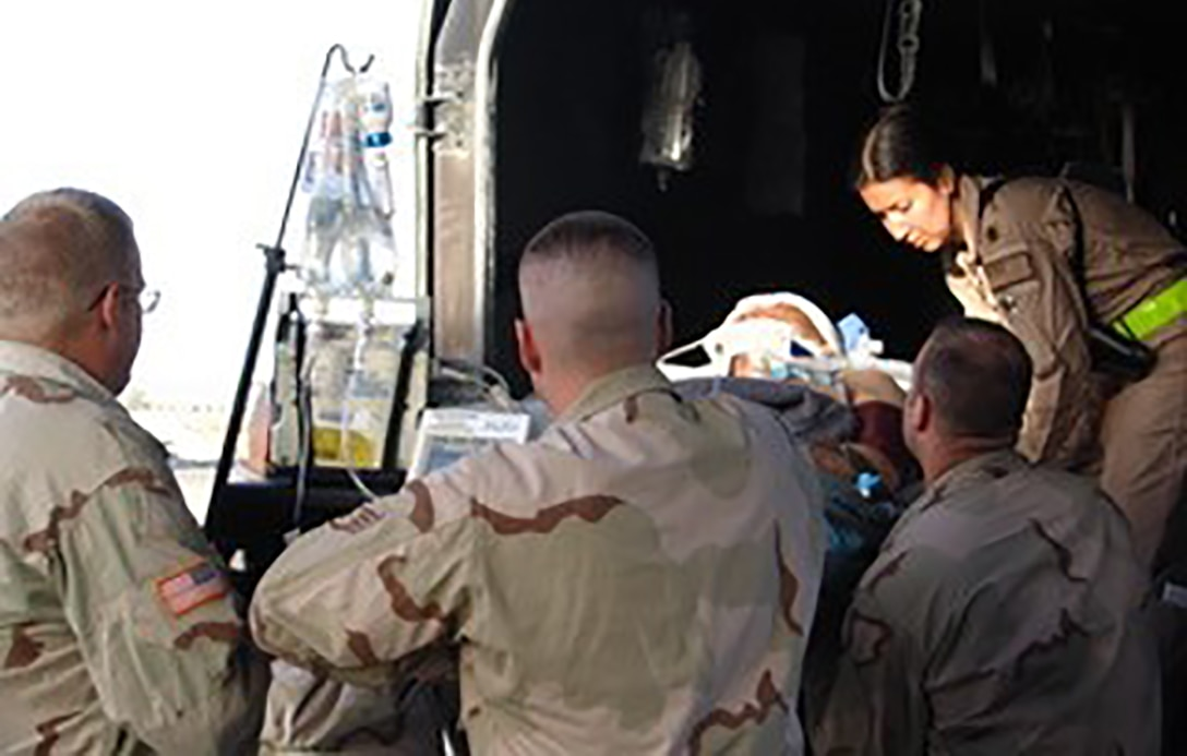Then Lt. Col. Maria Angles, leading a Critical Care Air Transport Team, helps load a critically injured member in Kandahar, Iraq, in 2005