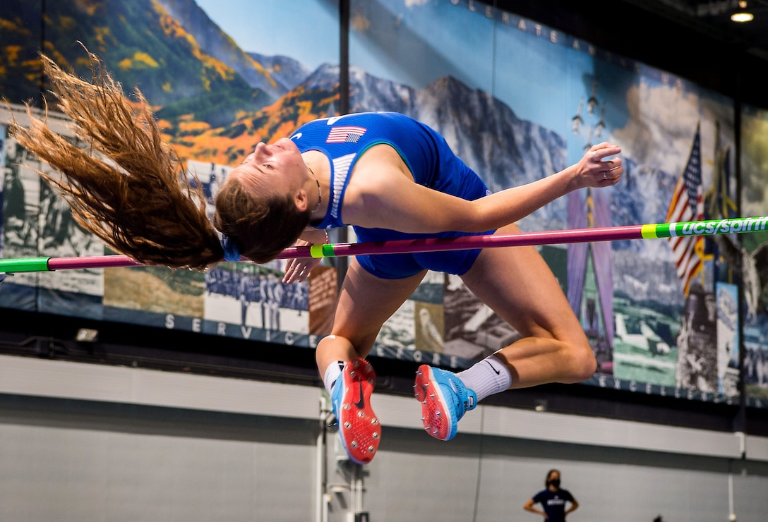 A woman arches her back as she jumps over a high bar.