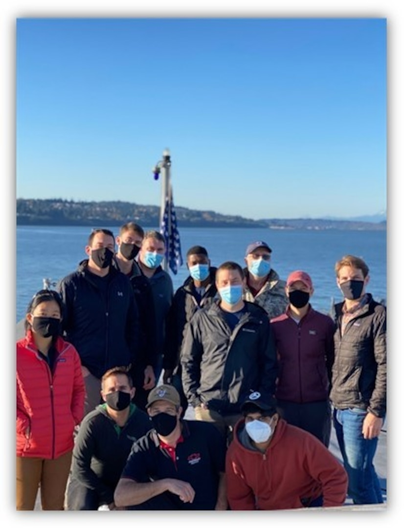 Naval Surface Warfare Center, Carderock and Philadelphia Division employees take a group photo on the bow of USS Zumwalt (DDG 1000) while in port on Nov. 8, 2020 in Everett, Washington.