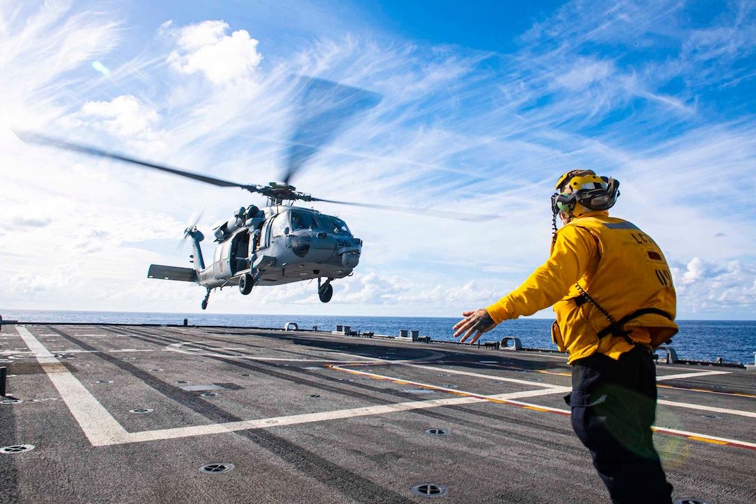 A sailor signals to a helicopter on the deck of a ship.