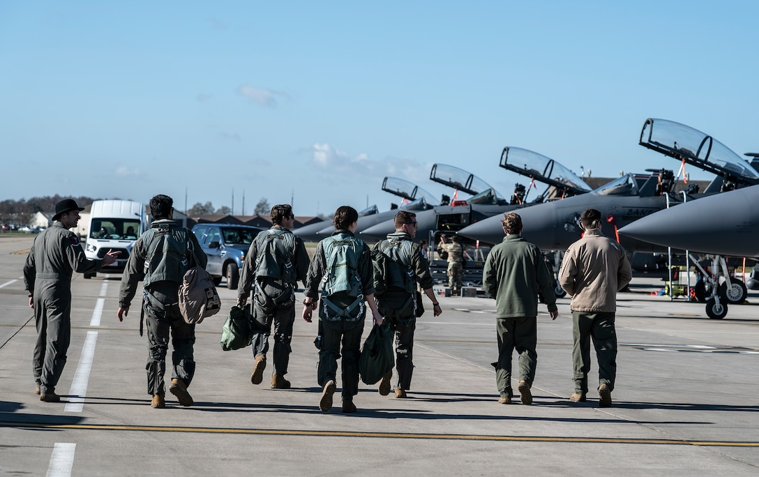 Aircrew assigned to the 492nd Fighter Squadron, along with Airmen who have been awarded orientation flights, step to their aircraft at Royal Air Force Lakenheath, England, Feb. 26, 2021. Orientation flights are offered to those who have responsibilities related to aviation and aircraft or as an award to individuals who show exceptional performance in their duties. (U.S. Air Force photo by Airman 1st Class Jessi Monte)