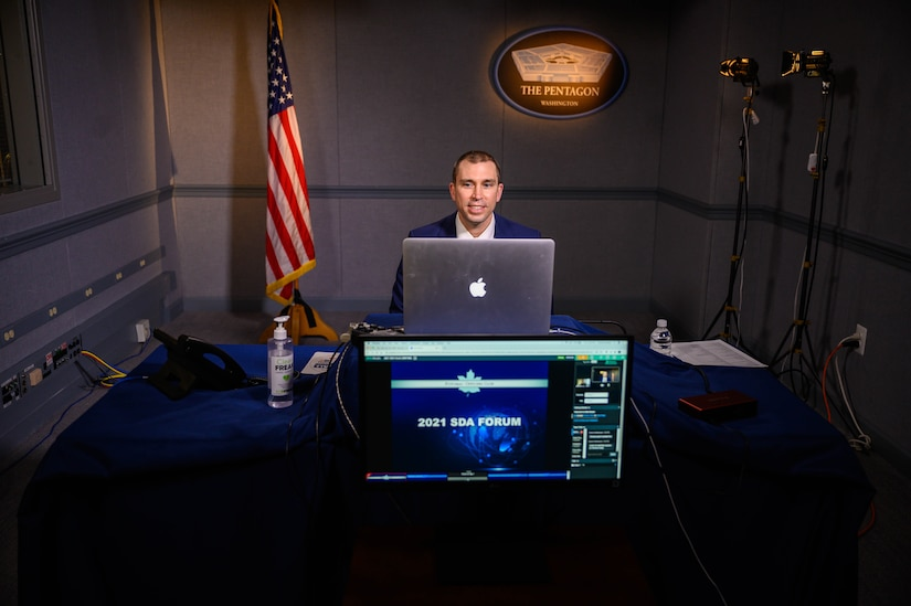 """A man sits behind a laptop computer and a television screen. The television screen says """"2021 SDA Forum.""""  In the background are a U.S. flag and a sign that says """"The Pentagon - Washington."""""""