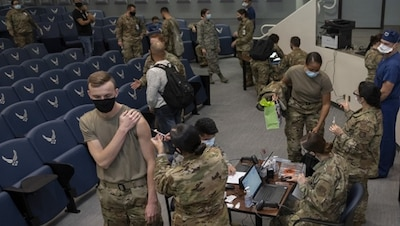 A soldier receives a vaccination in an auditorium full of people involved in distributing and receiving the vaccine.