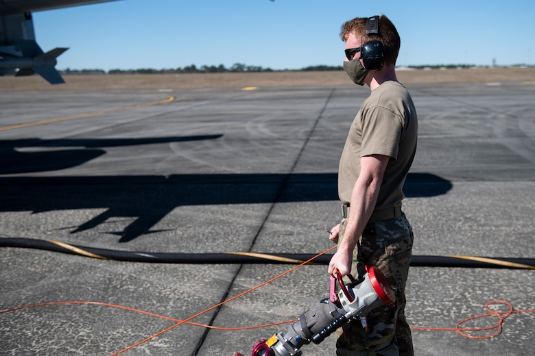 A photo of an Airman holding a fuel hose.
