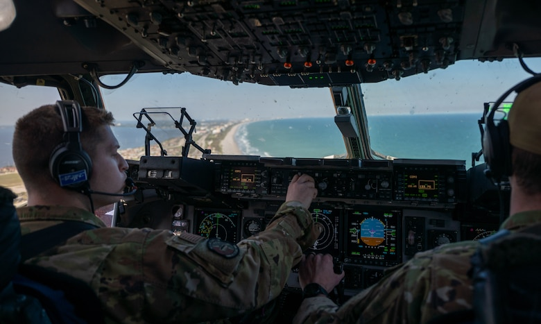 First Lt. August Hein (left) and Capt. Reed Fleming, both 3rd Airlift Squadron pilots from Dover Air Force Base fly a Dover AFB C-17 Globemaster III over Florida during Exercise Mosaic Tiger, Feb. 25, 2021. Mobility Airmen from Dover AFB and Joint Base McGuire-Dix-Lakehurst, New Jersey, participated in the exercise to enhance readiness and reinforce Air Mobility Command support to the joint warfighter. (U.S. Air Force photo by Airman 1st Class Faith Schaefer)