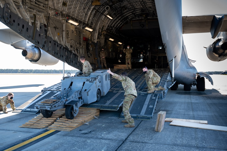 Airmen from Dover Air Force Base marshal a bomb loading cart onto a Dover AFB C-17 Globemaster III during exercise Mosaic Tiger at Moody AFB, Georgia, Feb. 23, 2021. Mobility Airmen from Dover AFB and Joint Base McGuire-Dix Lakehurst, New Jersey, participated in the exercise to enhance readiness and reinforce Air Mobility Command support to the joint warfighter. (U.S. Air Force photo by Airman 1st Class Faith Schaefer)