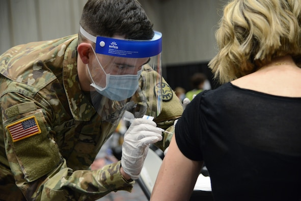 Oregon Army National Guard Sgt. Ryan Kill administers the COVID-19 vaccine to a walk-in patient at the Oregon Convention Center, Portland, Ore., Jan. 27, 2021. Guard members are helping local partners throughout the state respond to the pandemic.