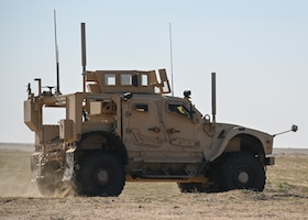 A photo of a Humvee driving in the desert