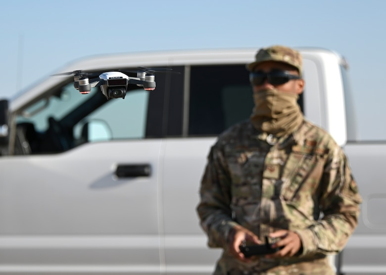A photo of an Airman flying a drone