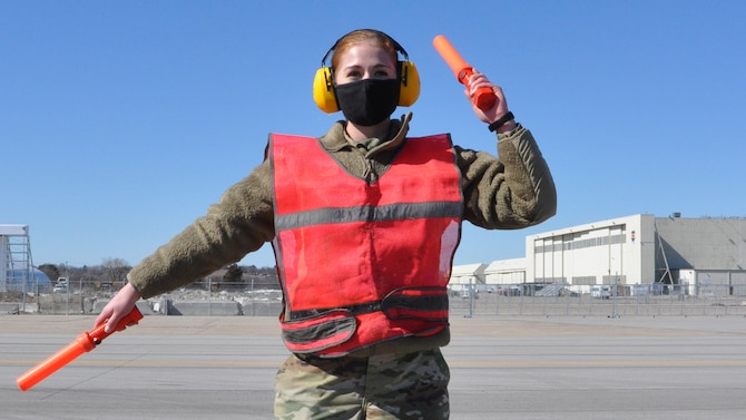 Air Force female wearing COVID-19 protective mask, ear protection headphones, in uniform, wearing an orange vest and carrying an orange signal lights in each hand directing an aircraft