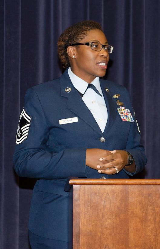female Air Force Senior Master Sergeant standing behind a podium speaking