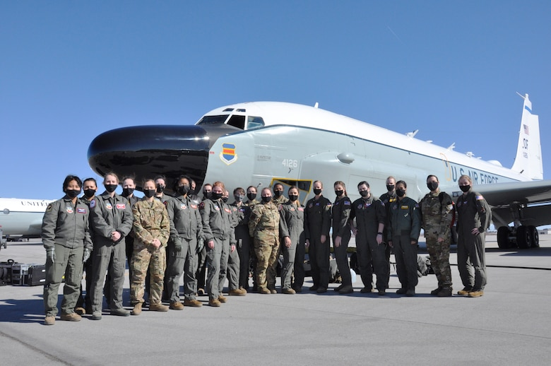 a group of 23 women air crew and support staff in uniform standing together in front of an RC-135 Rivet Joint aircraft