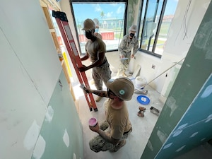 Seabees repair drywall during a remodel at Naval Air Station Key West.