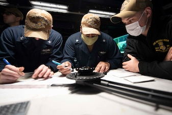 Sailors plot targets during a naval surface fire support (NSFS) exercise aboard USS Mitscher (DDG 57).