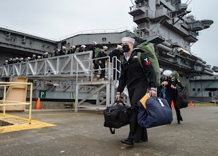 Sailors disembark the aircraft carrier USS Nimitz (CVN 68).