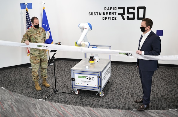 Lt. Gen. Shaun Morris, Air Force Life Cycle Management Center Commander (left) and Nathan Parker, RSO Deputy Program Executive Officer, with the help of a robotic arm, cut the ribbon on Hangar01, a new RSO workspace in Dayton, Ohio on March 2, 2021. (U.S. Air Force photo by Casey Tromp).