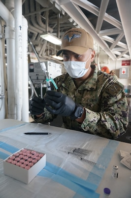 Hospital Corpsman 2nd Class Justin Yabut, from Las Vegas, prepares COVID-19 vaccines aboard the Ticonderoga-class guided-missile cruiser USS Lake Champlain (CG 57).
