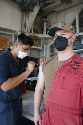 Hull Maintenance Technician 2nd Class Wane Debatin, right, receives the COVID-19 vaccine from Hospitalman Edward Velez, from Torrance, Calif., aboard USS Lake Champlain (CG 57).