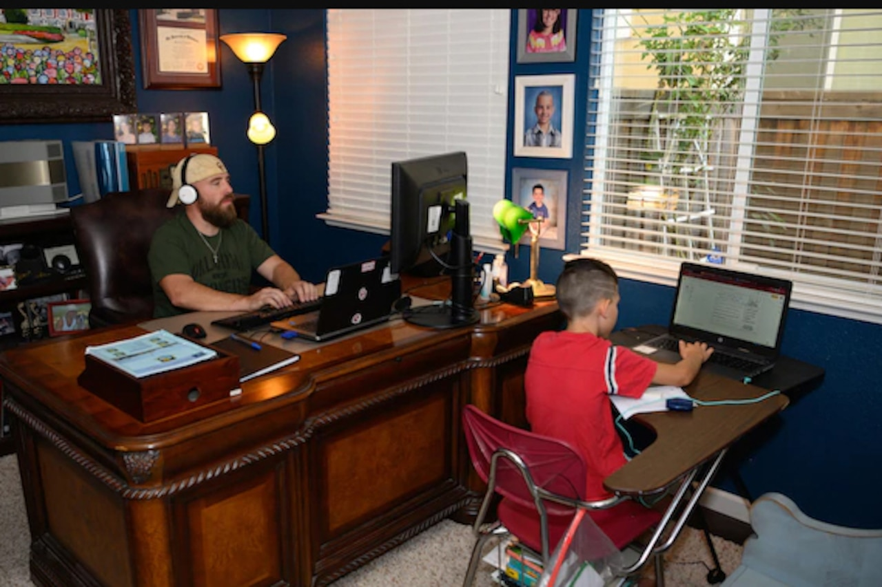 A father and son each sit at a desk in a shared home-office.