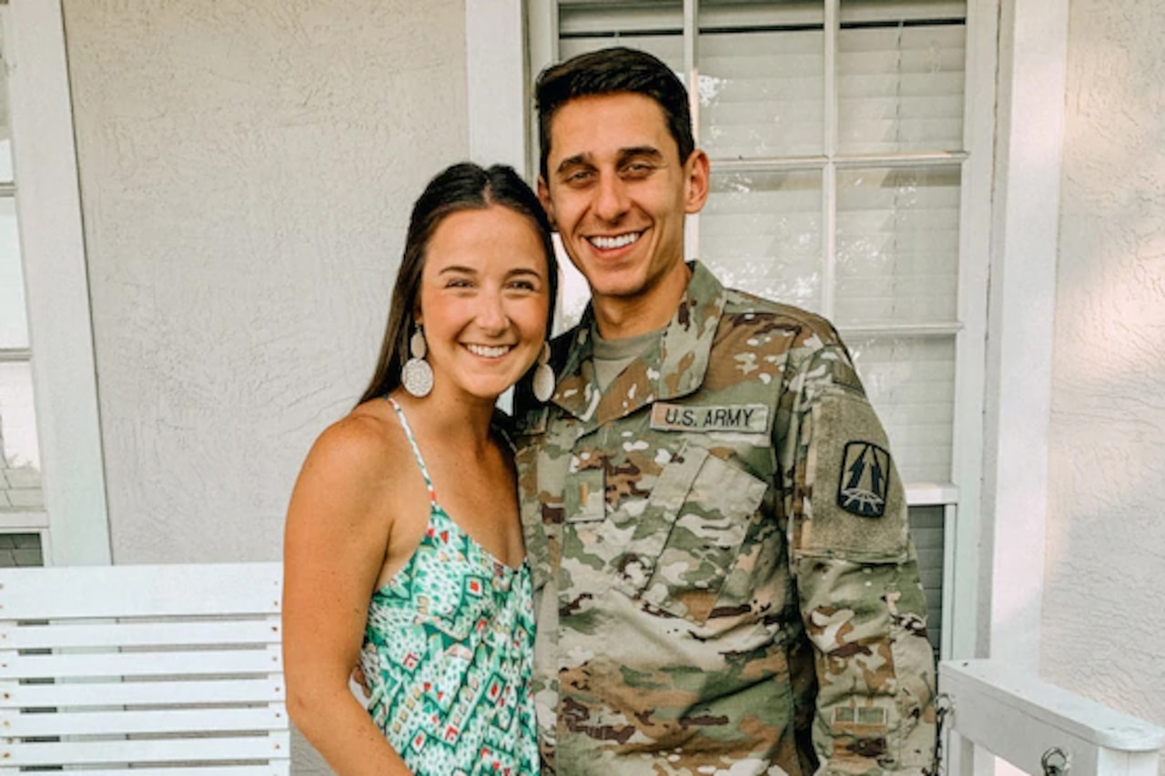 A man in military uniform poses for a photo with a woman.