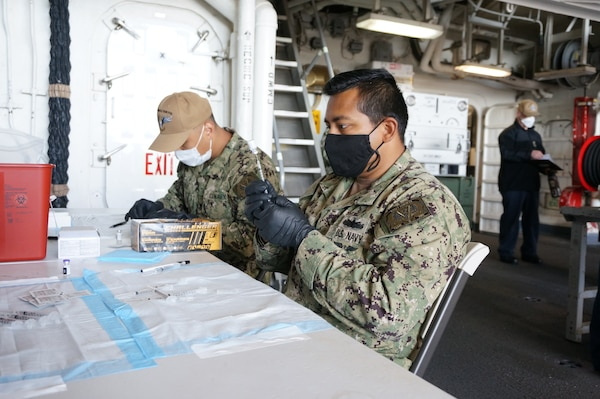Hospital Corpsman 3rd Class Quincy Godina, from Victorville, Calif., prepares COVID-19 vaccines aboard the Ticonderoga-class guided-missile cruiser USS Lake Champlain (CG 57).