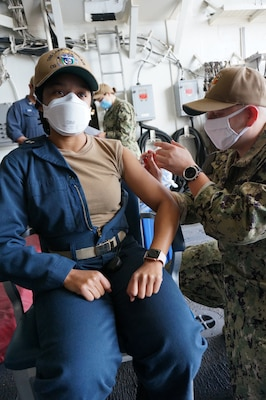 Lt. Cynthia Nestor, left, from Silver Spring, Md., receives the COVID-19 vaccine from Hospital Corpsman 2nd Class Jorge Casasola, from Houston, aboard  USS Lake Champlain (CG 57).