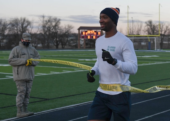 An Airman crosses the finish line to the Great American Spit Out 5k at the track.