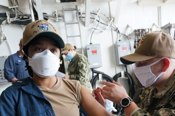 SAN DIEGO (Mar. 4, 2021) Lt. Cynthia Nestor, left, a native of Silver Spring, Md., receives the COVID-19 vaccine from Hospital Corpsman 2nd Class Jorge Casasola, a native of Houston, aboard Ticonderoga-class cruiser USS Lake Champlain (CG 57). Vaccines were administered to over 300 Lake Champlain Sailors who volunteered to receive the shot. Lake Champlain is currently pierside in its homeport of San Diego.