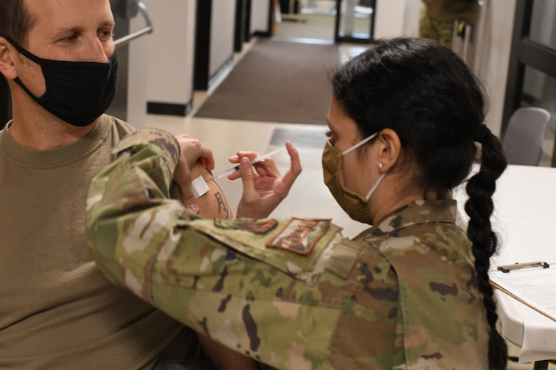 U.S. Air Force Col. David 'Moon' Halasi-Kun, vice-commander, 104th Fighter Wing, receives his COVID-19 vaccination from Staff Sgt. Daniela Rizzari, aeromedical technician, 104th Medical Group, at the base clinic on Feb. 23, 2021. Barnestormers have been stepping up to fight the COVID-19 pandemic by volunteering to get vaccinated. (U.S. Air National Guard photo by Staff Sgt. Hanna Smith)