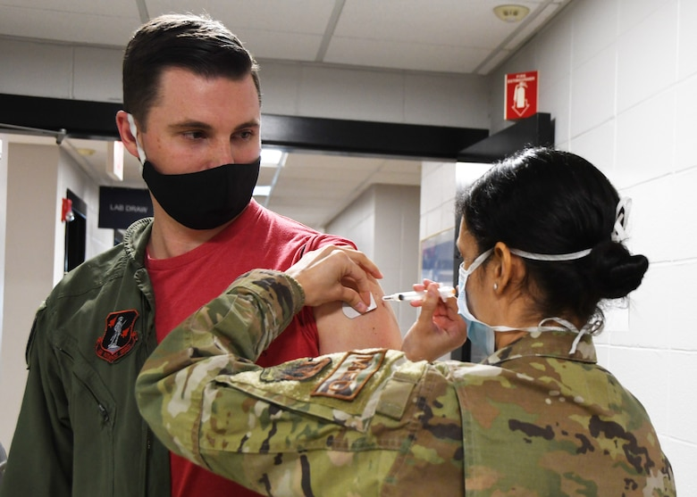 U.S. Air Force Maj. Michael 'BS' Walsh, a pilot with the 131st Fighter Squadron, receives his COVID-19 vaccination from Staff Sgt. Daniela Rizzari, an aeromedical technician with the 104th Medical Group, at the base clinic Feb. 5, 2021. Barnestormers have been stepping up to fight the COVID-19 pandemic by volunteering to get vaccinated.(U.S. Air National Guard photo by Staff Sgt. Hanna Smith)