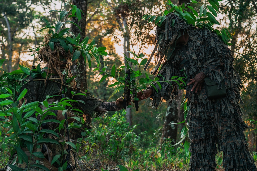 U.S. and Guatemalan troops dress in camouflage in the woods.