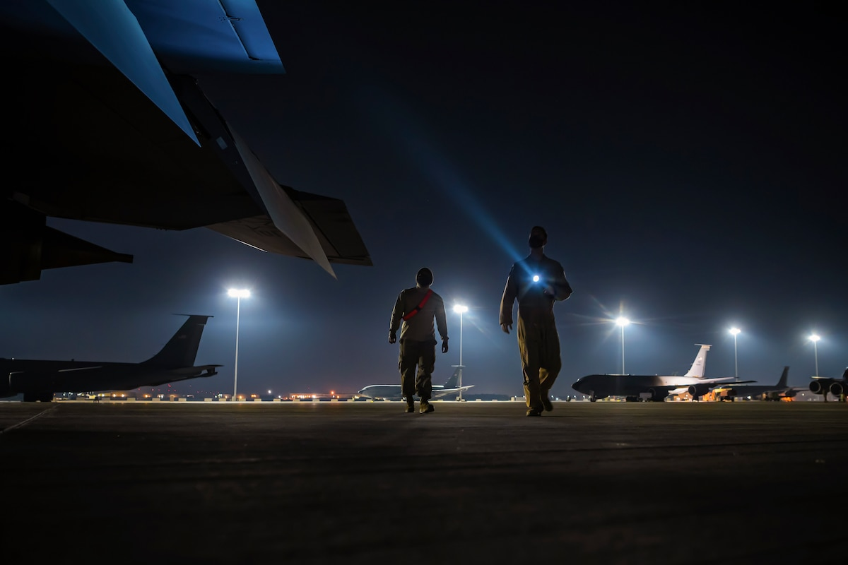 Two service members use a flashlight to walk around an aircraft in the dark.