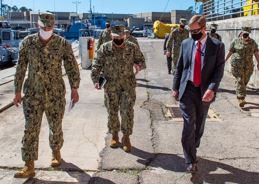 Capt. David Back (left), commanding officer at Naval Surface Warfare Center Panama City Division (NSWC PCD) and Dr. Peter Adair (right), NSWC PCD technical director provide a tour of unmanned systems with Adm. Mike Gilday, Chief of Naval Operations (center) March 4.