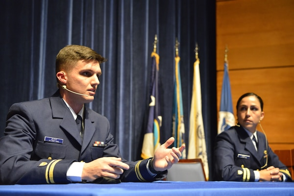 U.S. Coast Guard Lt. j.g. Justin Jezuit, prospective commanding officer of the Cutter Stingray, alongside Lt. Gabriella Deza, a helicopter pilot stationed in Borinquen, Puerto Rico, address cadets at the Coast Guard Academy, New London, Connecticut, March 3, 2021. Adm. Karl Shultz and the four other panelists discussed their own personal experiences in the field to give insight into what lies ahead once the cadets join the fleet as officers. (U.S. Coast Guard photo by Petty Officer 2nd Class Ronald Hodges)