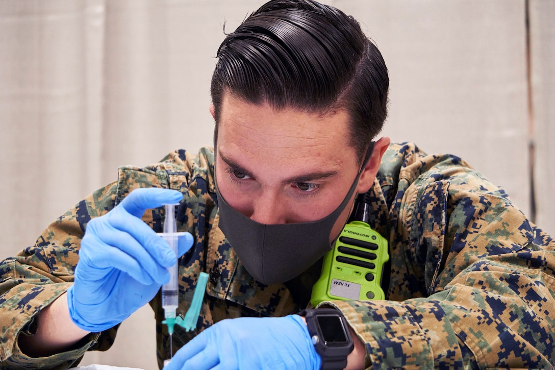 A sailor wearing a face mask and gloves holds a syringe  while preparing a COVID-19 vaccine.