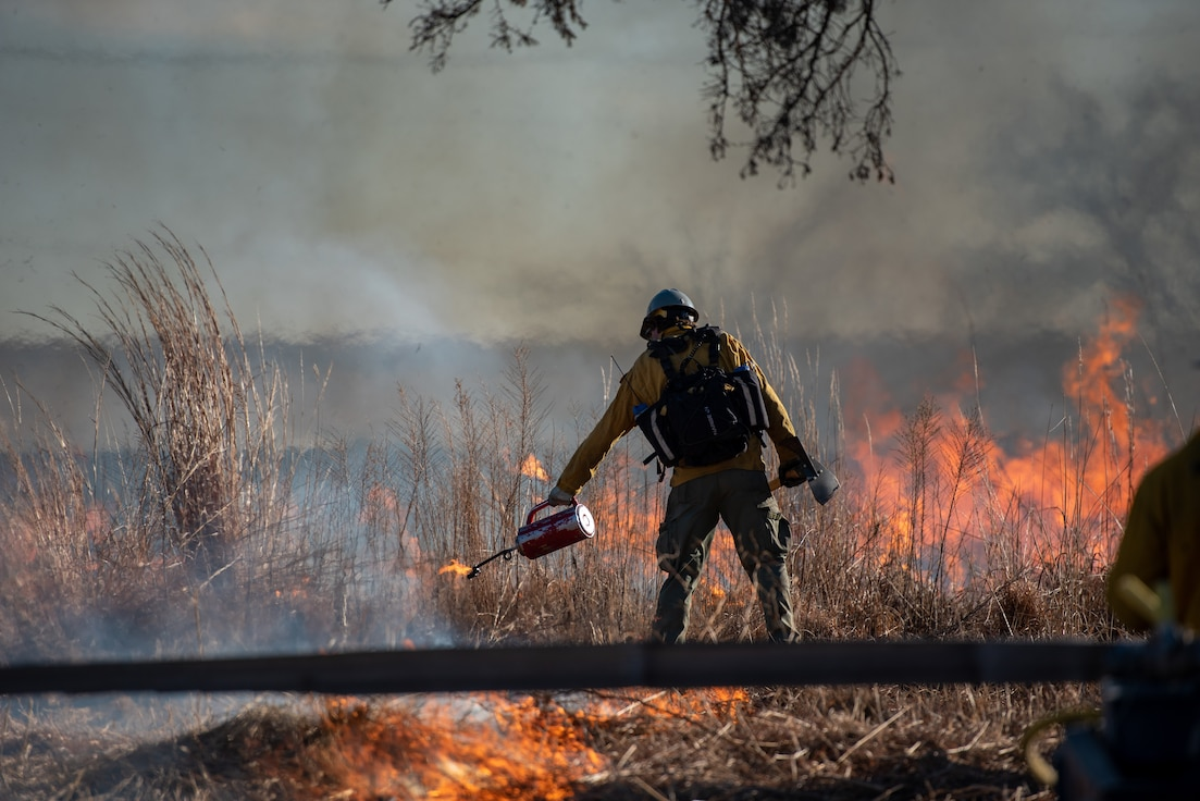 A member of the Air Force Wildland Fire Center uses a torch to light a controlled fire