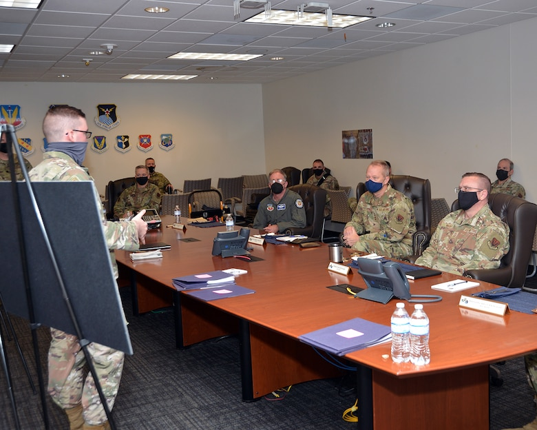An officer in uniform briefs leadership in uniform around a table.