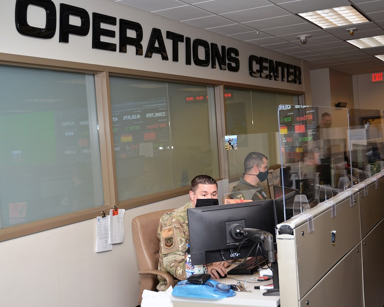 Airmen in uniform type on computers in an operations center.